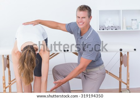 Happy doctor stretching a woman back in medical office - stock photo