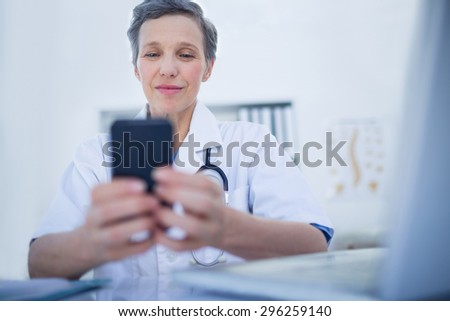 Happy doctor using her smartphone in medical office - stock photo