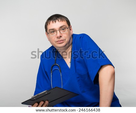 Happy doctor with clipboard, on a gray background - stock photo