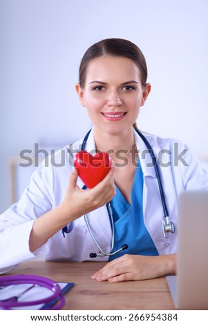 Happy doctor with red heart symbol at desk  - stock photo