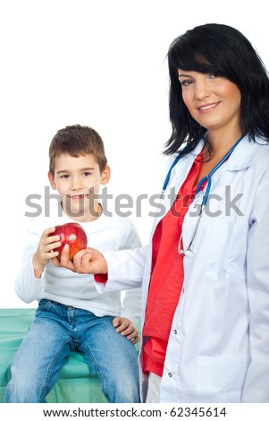 Happy doctor woman giving a red apple to a smiling child with missing teeth - stock photo