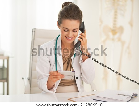Happy doctor woman with calculator talking phone - stock photo