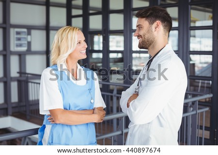 Happy doctors discussing while standing at hospital - stock photo
