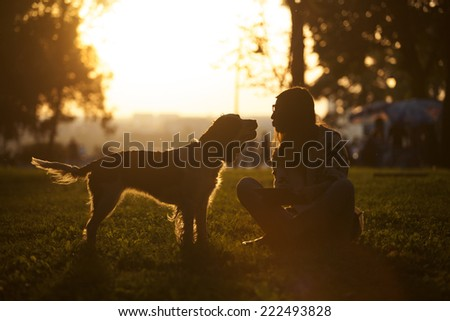 Happy Dog And Young Girl Sitting On The Grass In The Park At Sunset - stock photo
