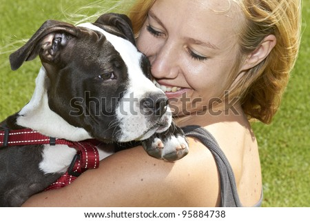 Happy dog owner with her Pit Bull puppy - stock photo