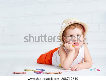 happy dreamy little artist  girl in a hat draws pencil lying on the floor - stock photo