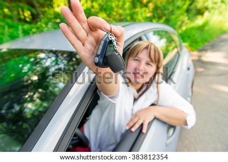 Happy driver showing the key of the rental car