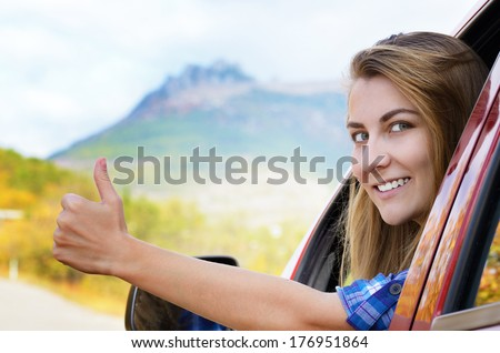 Happy driver woman shows thumb up against mountains background. Car insurance concept  - stock photo