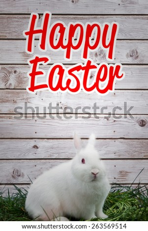happy easter against fluffy white bunny rabbit sitting on grass - stock photo