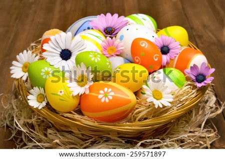 Happy Easter arrangement with a basket filled with colorfully painted eggs and little spring flowers