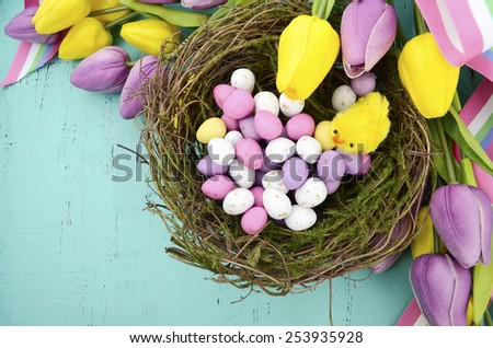Happy Easter background with painted Easter eggs in birds nest, and yellow and purple silk tulips and ribbon on vintage rustic distressed aqua blue wood table, with copy space for your text here. - stock photo