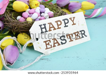 Happy Easter background with painted Easter eggs in birds nest, and yellow and purple silk tulips and ribbon on vintage style rustic distressed aqua blue wood table, with greeting tag, closeup.