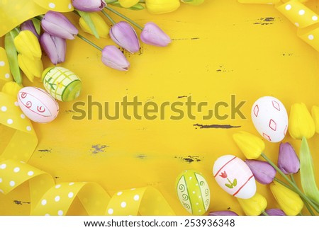 Happy Easter background with painted Easter eggs, yellow and purple silk tulips and polka dot ribbon on vintage style rustic distressed yellow wood table, with copy space for your text here. - stock photo