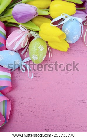 Happy Easter background with painted Easter eggs, yellow and purple silk tulips and ribbon on vintage style rustic distressed pink wood table, with copy space for your text here, vertical. - stock photo