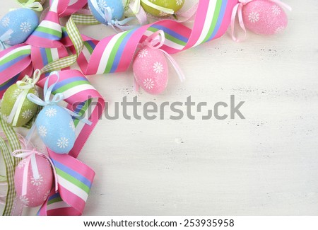 Happy Easter background with pink, blue and green ornament eggs and ribbon on vintage style rustic distressed white shabby chic wood table, with copy space for your text here. - stock photo