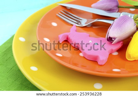 Happy Easter bright color orange, yellow and green polka dot theme table place setting with pink fondant bunny cookie and tulips on pale aqua blue distressed wood table, closeup. - stock photo