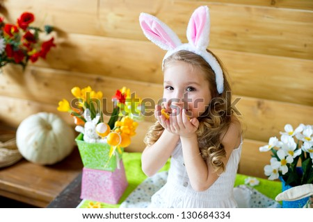 Happy easter bunny girl with colorful eggs sitting in country house and celebrating holiday - stock photo