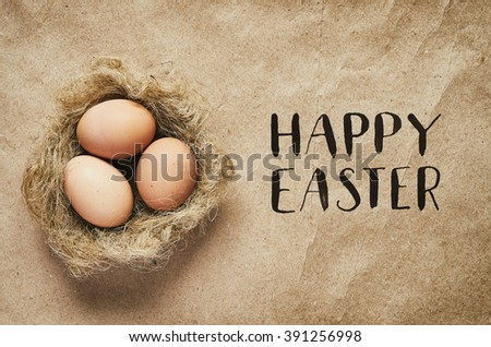 Happy Easter calligraphy. Nest with eggs on eco craft paper background. Easter postcard template. Space for text, copy, lettering. - stock photo