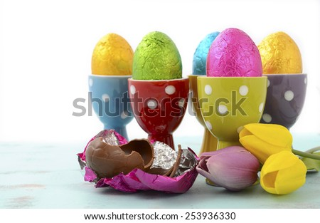 Happy Easter chocolate eggs wrapped in bright color foil in red, yellow, blue, green and purple polka dot egg cups. - stock photo