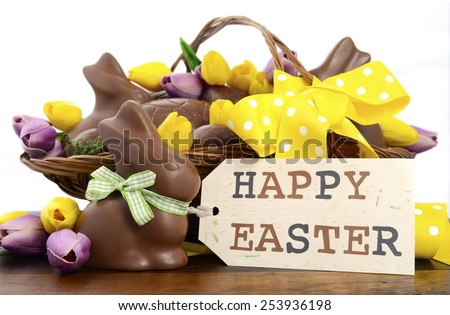 Happy Easter chocolate hamper of eggs and bunny rabbits in large basket with yellow and pink purple silk tulip flowers on dark wood table, with gift tag. - stock photo