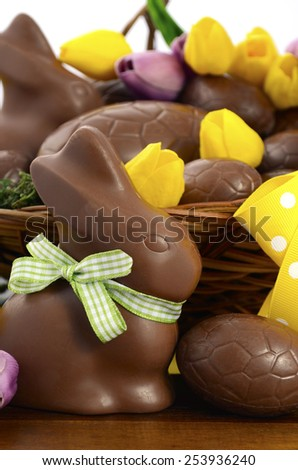 Happy Easter chocolate hamper of eggs and bunny rabbits in large basket with yellow and pink purple silk tulip flowers on dark wood table, closeup vertical. - stock photo