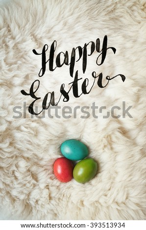 Happy Easter. Colored eggs on natural fluffy sheep skin background. Easter postcard template. Space for text, copy, lettering. - stock photo