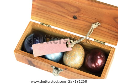 Happy easter. Colorful easter eggs in wood box on white background with blank tag space for text.