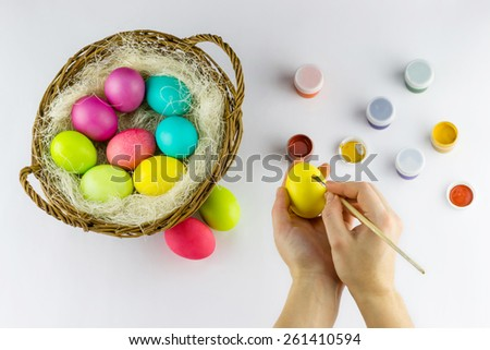 Happy Easter concept. Top view of female hands painting Easter egg with basket full of colorful painted eggs and tubes on white background - stock photo