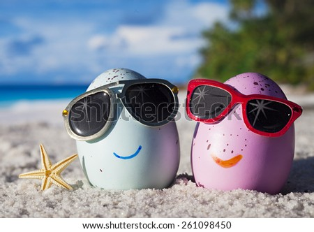 Happy easter eggs with sunglasses on ocean beach  - stock photo