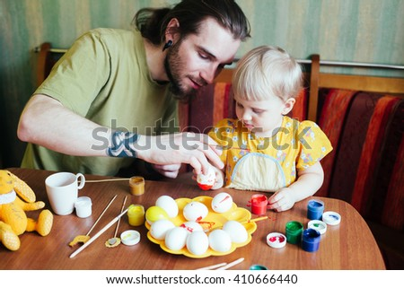 Happy easter!  Father and his daughter painting Easter eggs. Happy family preparing for Easter.