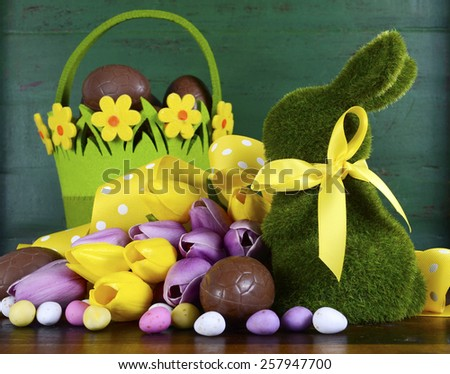 Happy Easter green moss grass bunny rabbit with basket of chocolate eggs and spring tulips against a green wood background.  - stock photo