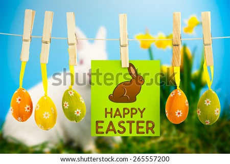 Happy Easter greeting against white fluffy bunny sitting beside daffodils with easter eggs - stock photo