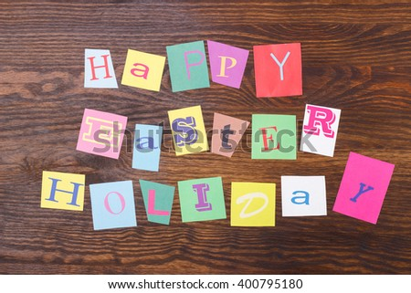 Happy Easter holiday: collage from colorful paper letters, wooden background