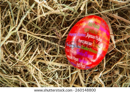 Happy easter in different languages against red egg on straw - stock photo