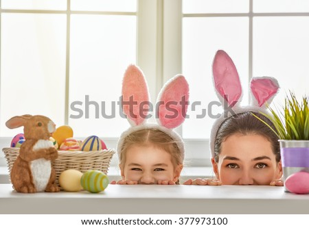 Happy easter! Mother and daughter begin to hunt for Easter eggs. Happy family preparing for Easter. Cute little child girl wearing bunny ears on Easter day. - stock photo