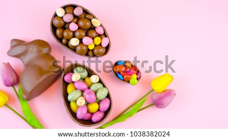 Happy Easter overhead with chocolate Easter eggs and decorations on a wood table background