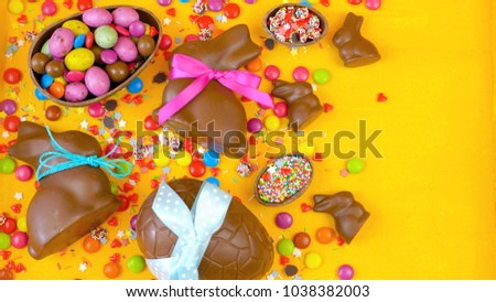 Happy Easter overhead with chocolate Easter eggs and decorations on a wood table background with copy space.
