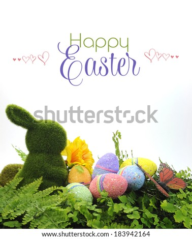 Happy Easter scene with moss bunny and colorful glitter eggs, daffodil and butterfly on ferns with sample text or copy space for your text here. - stock photo
