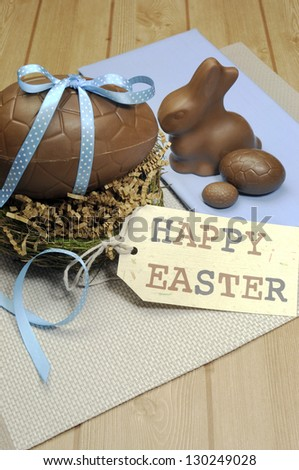 Happy Easter still life with chocolate eggs, bunny and gift tag on wood table. Vertical with copy space. - stock photo