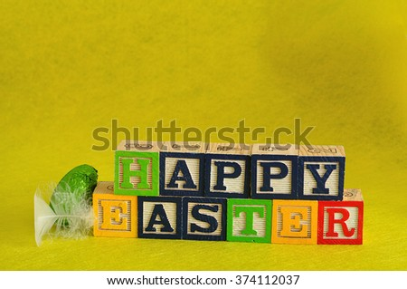 Happy easter with colorful alphabet blocks, shiny wrapped easter eggs and a feather isolated against a yellow background