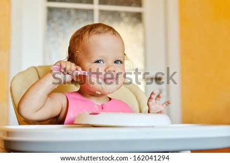 happy eating baby girl with dirty face - stock photo