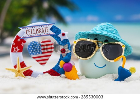 Happy egg with word celebrate  on ocean beach during patriotic holiday â?? 4th of july