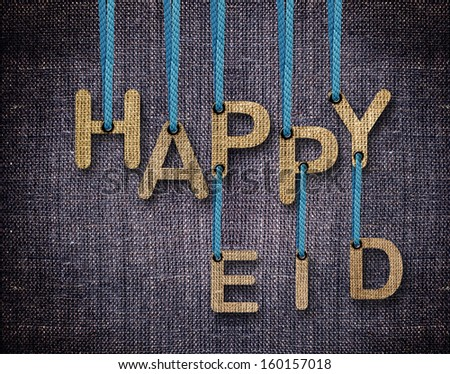 Happy Eid letters hanging strings with blue sackcloth background. - stock photo