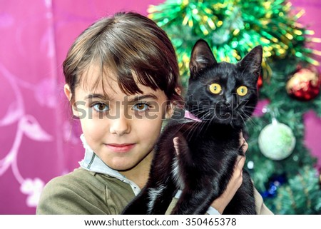 Happy  eight year old girl with black cat for Christmas gift - stock photo