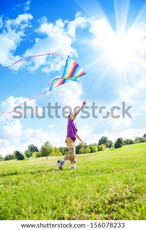 Happy eight years old nice boy playing in field with big color kite