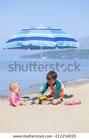 Happy elder brother is playing with his younger pretty sister on sand near sea - stock photo