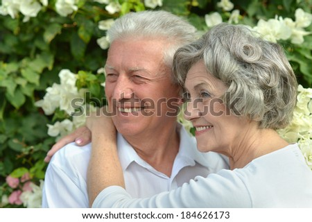 Happy elder couple resting on pink flowers background