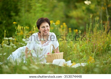 Happy elder woman resting on grass at nature - stock photo