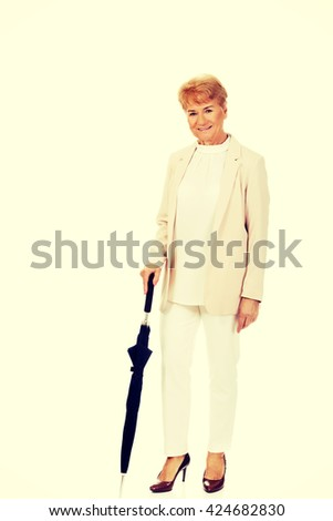 Happy elderly business woman holding an umbrella