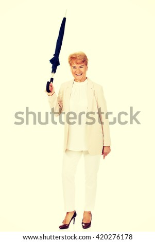 Happy elderly business woman pointing up with umbrella - stock photo